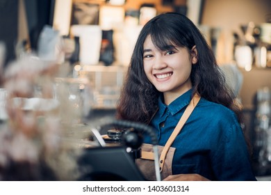 asian woman barista making hot coffee with machine at counter bar and smile at camera in cafe restaurant,Food and drink service concept.
