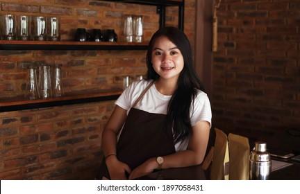 Asian woman barista smilling look camera at cafe