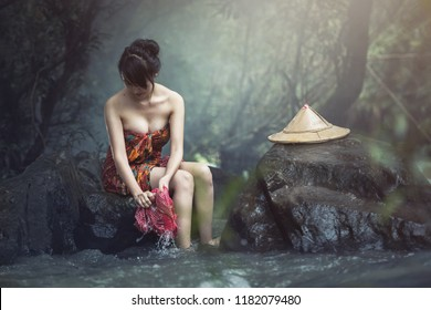 Asian woman was bathing in the brook, washing in the creek, country girl portrait in outdoors, Thailand