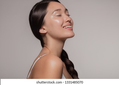Asian woman with beautiful and healthy skin on beige background. Girl smiling with her eyes closed.
