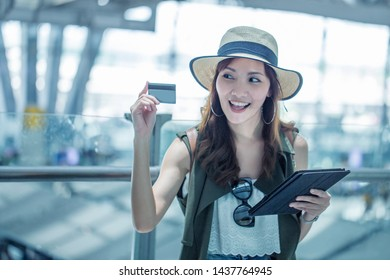 Asian woman, beautiful woman holding a credit card, spending Convenient for traveling during holidays, traveling at the airport.Vacation and Travel concept.
