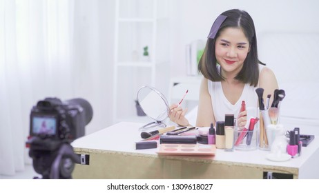 Asian woman beauty blogger,vlogger smaile to camera while applying lipstick to her mouth doing cosmetic makeup tutorial