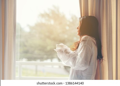 Asian woman in bedroom drinking coffee after wake up near window, sunny morning.  Lifestyle Concept.