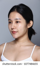 Asian Woman before applying make up hair style. no retouch, fresh face with nice and smooth skin. Studio lighting gray background