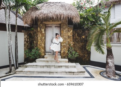Asian woman with black curly hair enjoying in private villa in Canggu. Wearing white light tunic, barefoot. Casual style, tropical garden. Sunny weather