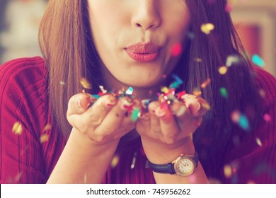 Asian woman blowing glitter, celebration concept.