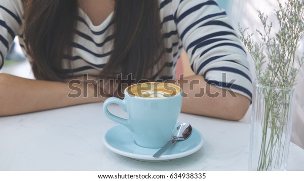 An Asian woman and a blue hot coffee cup on marble table in modern cafe