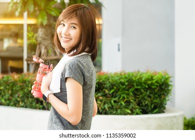 Asian woman with bottle of water rest after exercise in afternoon