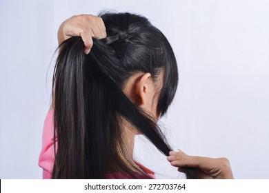 Asian woman braiding hair.
