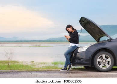 Asian woman with a broken car with open hood.Young woman using mobile phone while looking at broken down car on street