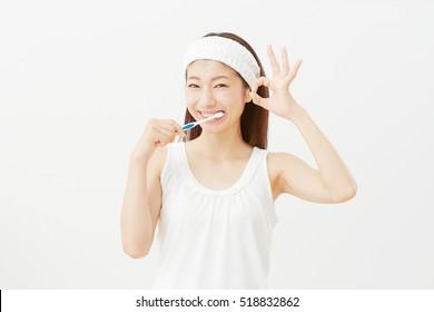 Asian woman brushing her teeth