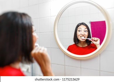 Asian woman brushing teeth and looking in the mirror in the bathroom in her apartment