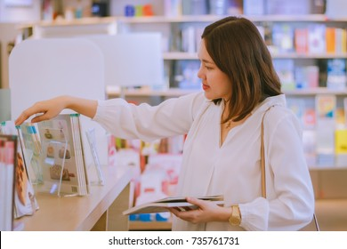Asian woman buying bakery recipe book at store