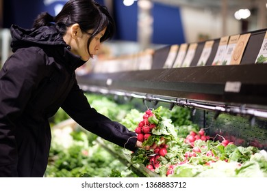 Asian woman buying, holding and choosing fresh vegetable in grocery store.