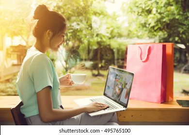 Asian woman buying from an online store. She was at a coffee shop