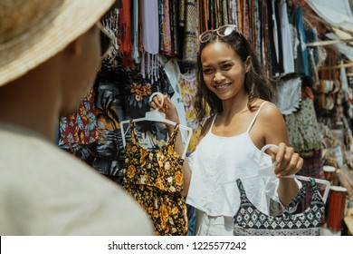 asian woman buying some clothes in souvenir shop while having trip to bali
