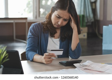 Asian woman calculating monthly expense and credit card debt.