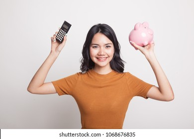 Asian woman with calculator and piggy bank on white background