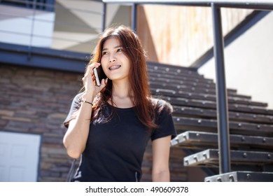 Asian woman calling phone with bright day
