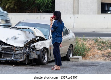 Asian woman calls for help and for insurance agent to quick attention in the spot of accident after cars crashed occurrence on road.