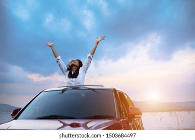 Asian woman in car with raised hands driving on sunset