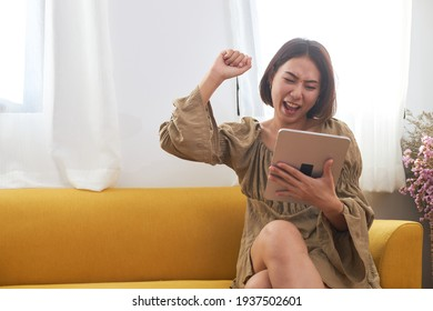 An Asian woman in casual clothing was holding and looking at her digital tablet, showing excruciating joy when she received the good news.