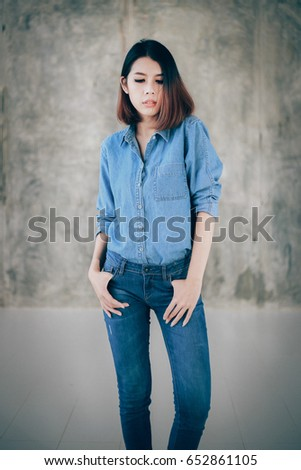 a538ca967b Asian woman casual outfits standing in jeans and blue denim shirt and holds  his hands in