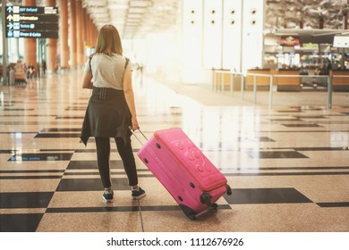 Asian woman in casual style looking for flight schedule board in airport terminal - travel concept