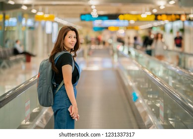 Asian woman in casual style using smartphone and looking for flight schedule board while moving walkway in airport terminal.