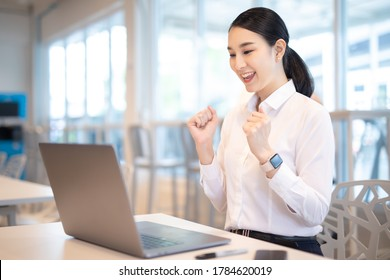 Asian woman celebrate with laptop, success happy pose. E-commerce, University education, internet Technology, or startup small business concept. Modern office or living room with copy space