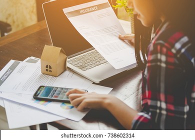 Asian woman check health insurance documents or various accidents and return value with the calculator While searching for information on law firms, consult the website before making a decision