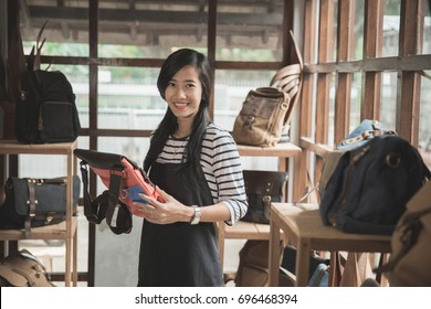 asian woman checking the quality of the product at her store