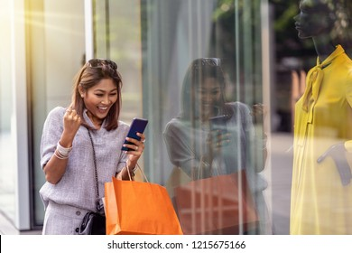 Asian woman cheerful when using the smart mobile phone for check online shopping order is completed with clothes beside the glassess in store shop with happy action at department center
