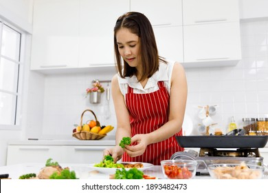 Asian woman chef in red apron putting parsley on steak in kitchen. Concept woman preparing meal at home.
