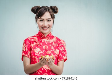 Asian woman with cheongsam holding gold. Chinese new year.