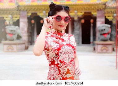 Asian woman in chinese dress traditional Cheongsam and Wear glasses. Happy Chinese New Year Concept