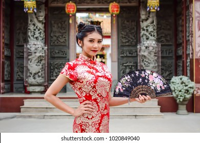 Asian woman in chinese dress traditional Cheongsam and holds the black fan. Happy Chinese New Year Concept