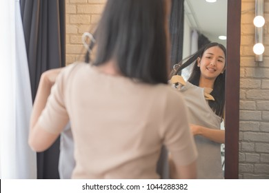 Asian woman choosing clothes and looking to mirror ,shopping and fashion concept
