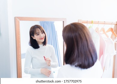 Asian woman choosing make up with cosmatic applying lipstick and smiling happy in front mirror at home people every day look lifestyle.