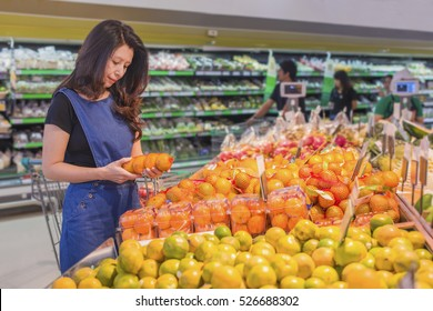 Asian woman choosing orange during shopping fruit vegetable at supermarket. (supermarket in blur for background)