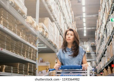 Asian woman choosing the right furniture for her apartment in furniture store, Decoration and Warehouse goods with shopping cart.
