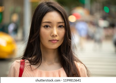 Asian woman in city serious sad face portrait