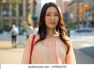 Asian woman in city walking street smile happy