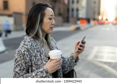 Asian woman in city walking street texting on cell phone