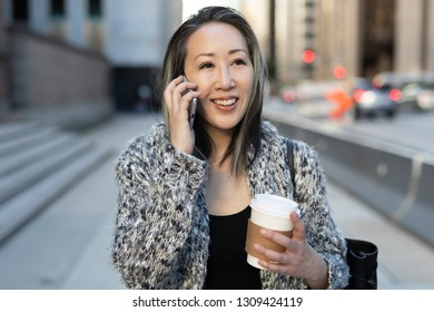 Asian woman in city walking talking on cell phone