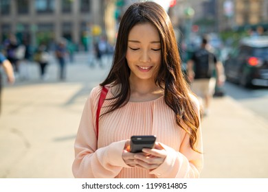 Asian woman in city walking using cell phone