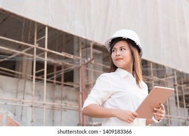 Asian woman civil engineer with white safety helmet visit construction site and holding tablet for checking working progress and drawing.