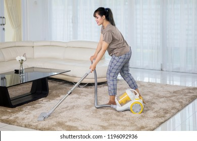 Asian woman cleaning carpet with a vacuum cleaner in the living room. Shot at home
