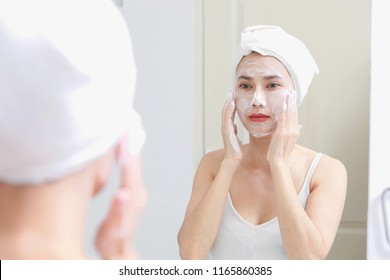 Asian woman cleaning face skin enjoy herself with bubble cleansing foam.
