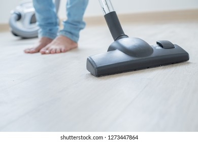 Asian woman cleaning the floor in the living room